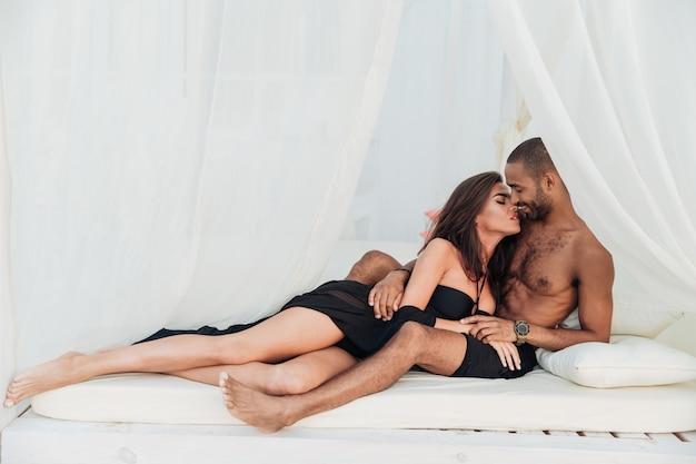 Mooi jong paar dat en op wit bed ligt kussen