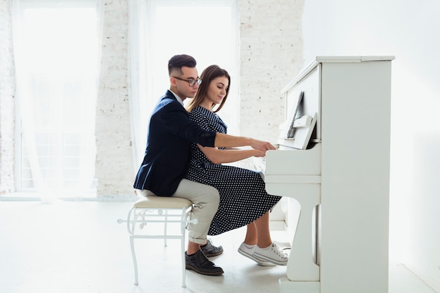Mooi jong paar die de piano samen thuis spelen