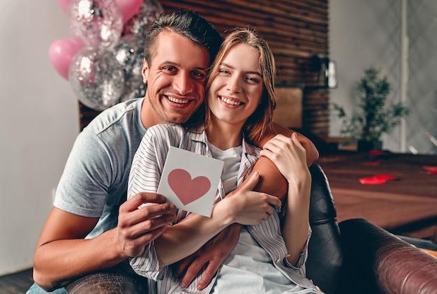 Mooi jong paar in slaapkamer met valentijnskaart.