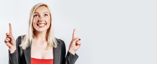 Mooi jong schattig meisje glimlachend wijzende vinger op grijze geïsoleerde achtergrond