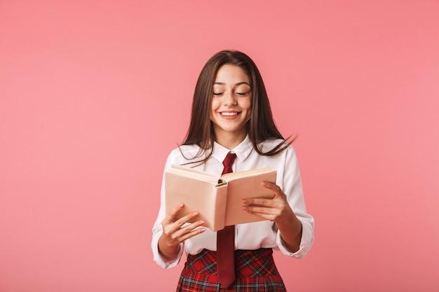 Mooi jong schoolmeisje die eenvormige status dragen die over roze muur wordt geïsoleerd