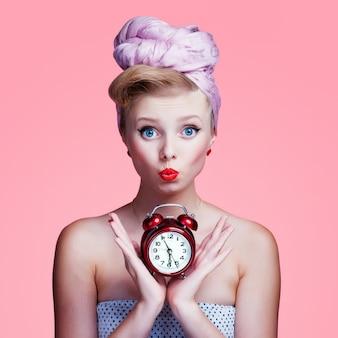 Mooi jong sexy speld-omhooggaand meisje met verraste uitdrukking, op roze achtergrond