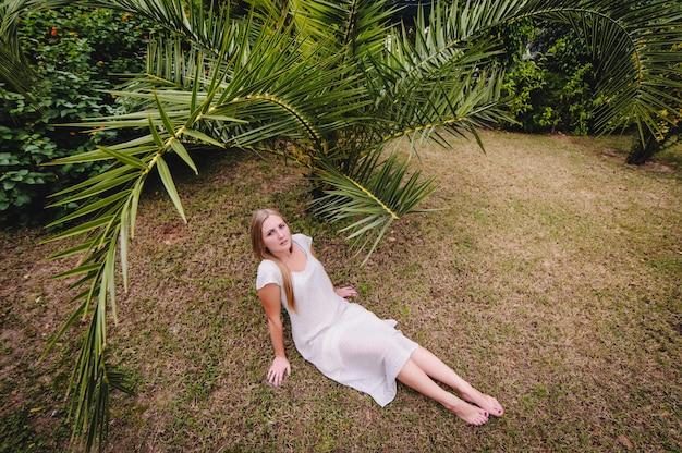 Mooi, jong, slank, langharig blond meisje in witte lange jurk