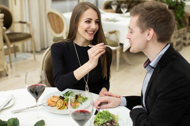 Mooi jong stel dat elkaar voedt en glimlacht terwijl ze tijd doorbrengt in het restaurant