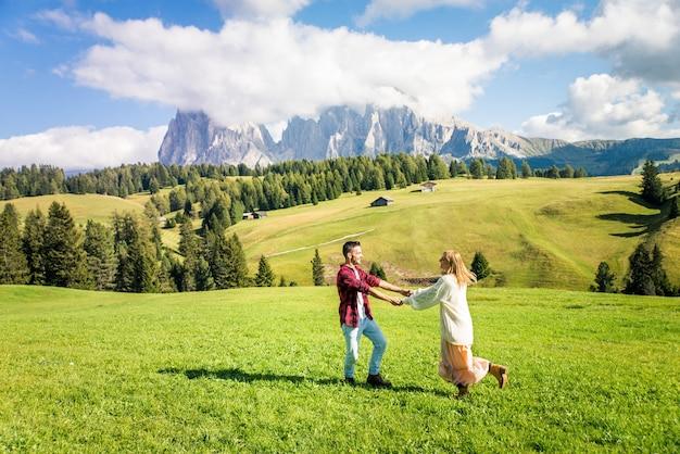 Mooi jong stel dat in de dolomieten italië reist. twee geliefden die een dagtocht in de natuur maken