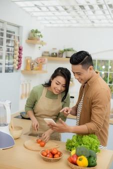Mooi jong stel gebruikt een mobiele telefoon en glimlacht terwijl ze thuis in de keuken kookt