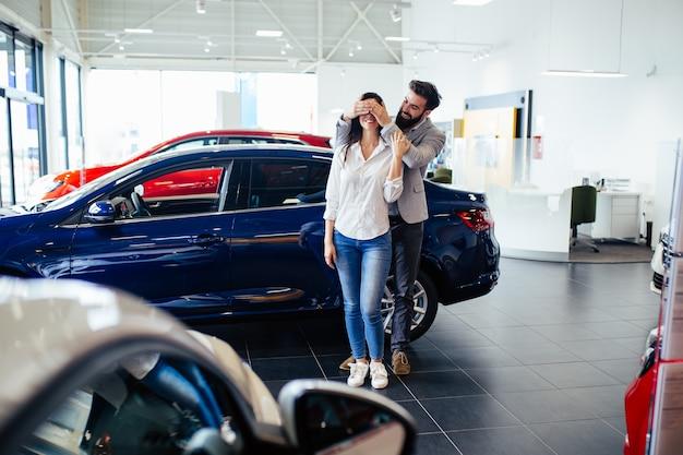 Mooi jong stel in autoshowroom die een nieuwe auto kiest om te kopen