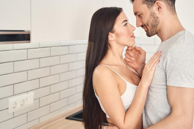 Mooi jong stel knuffelt en raakt elkaar teder aan in hun gezellige keuken terwijl ze een kus gaan hebben