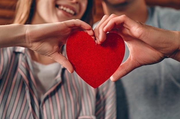 Mooi jong stel thuis. close-up beeld van een paar verliefd met een hart in hun handen
