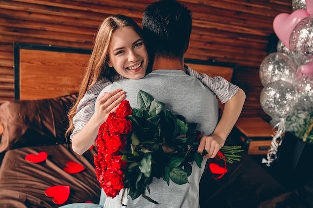 Mooi jong stel thuis. knuffelen, zoenen en genieten van tijd samen doorbrengen terwijl je valentijnsdag viert met rode rozen en luchtballonnen.