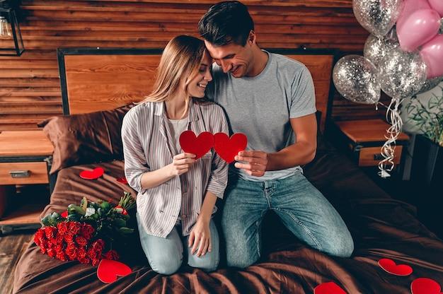 Mooi jong stel thuis. verliefde paar met harten in hun handen, knuffelen, kussen en genieten van tijd samen doorbrengen
