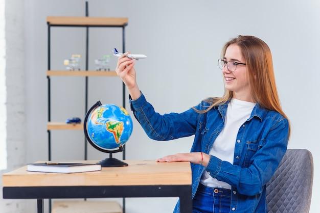 Mooi jong studentenmeisje dat pret heeft terwijl het verkennen van de bol met model van vliegtuig. aardrijkskunde studeren met globe.