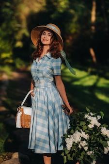 Mooi jong teder meisje in een strooien hoed met een boeket bloemen