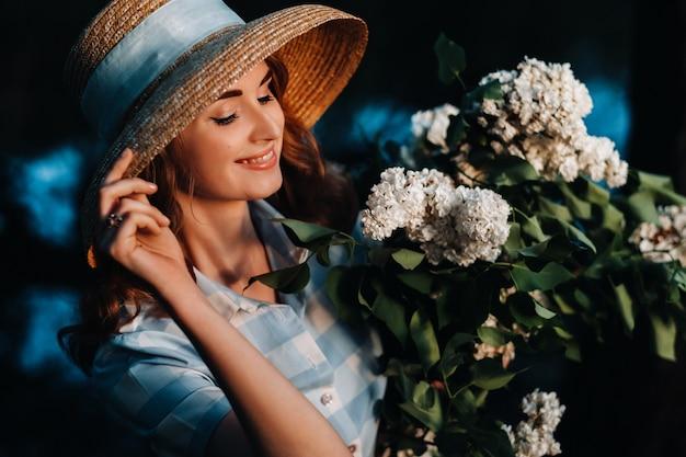 Mooi jong teder meisje met een boeket bloemen. charmante jonge dame met een boeket seringen. lila. mooie afgestudeerde in lila.