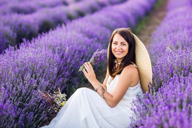 Mooi jong tienermeisje buitenshuis portret. brunette in hoed met mand bloemen oogsten in lavendel veld provence, bij zonsondergang. aantrekkelijk mooi meisje met lang haar.