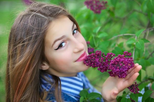 Mooi jong tienermeisje dat zich in de bloemen van sering bevindt.