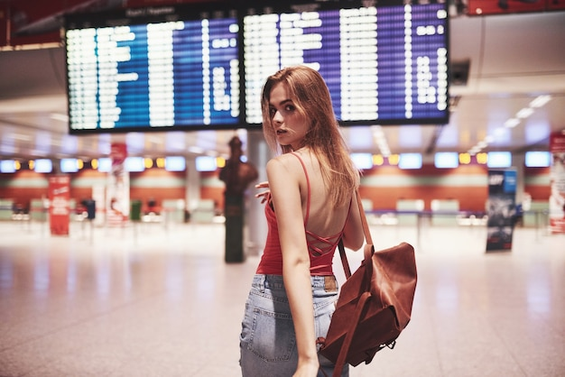 Mooi jong toeristenmeisje met rugzak in internationale luchthaven, dichtbij vluchtinformatiebord.