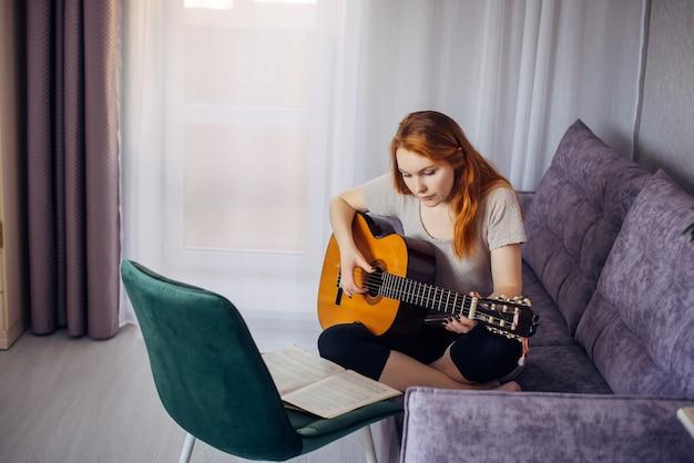 Mooi jong volwassen meisje met lang haar dat gitaar speelt, thuis op de bank zit, selectieve focus. serieuze vrouw tokkelt de snaren en bestudeert de melodie. thuis vrije tijd, hobby's, zelfontplooiing.