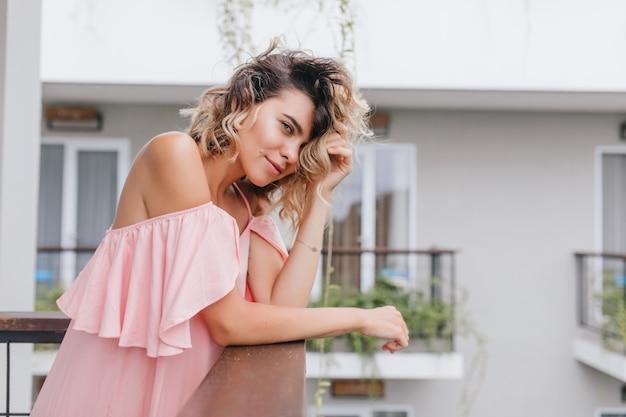 Mooi jong vrouwelijk model dat zich in weekendochtend bij balkon bevindt. verfijnd blondemeisje met krullend haar dat in hotel koelen.