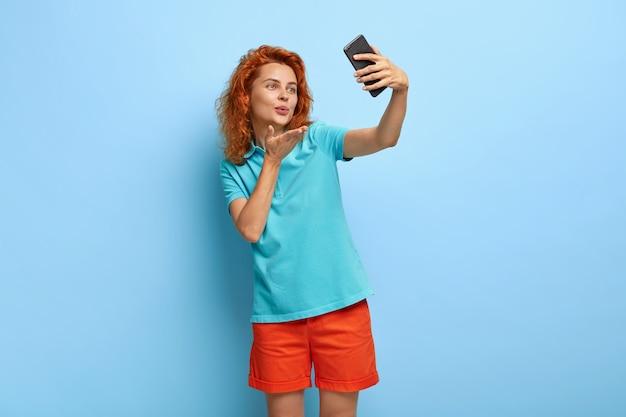 Mooi jong vrouwelijk model stuurt luchtkus op camera van mobiele telefoon, maakt selfie-portret om foto voor vriend te delen
