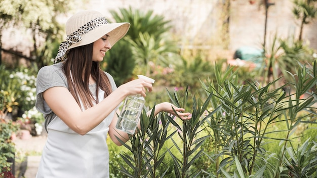 Mooi jong vrouwen bespuitend water van fles bij het kweken van installaties