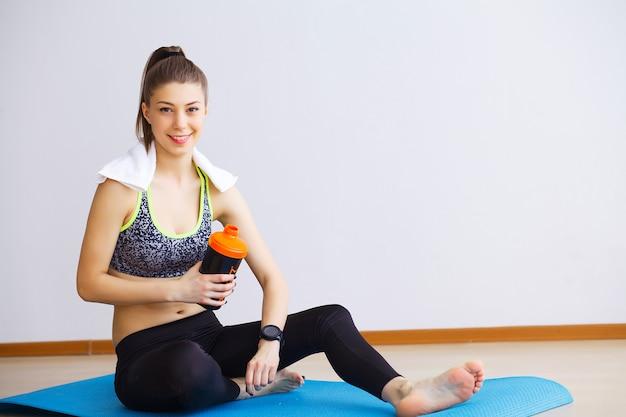 Mooi jong vrouwen rusten en drinkwater in de gymnastiek