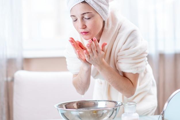 Mooi jong vrouwenwassen en verfrissend gezicht met water in de ochtend. concept van hygiëne en zorg voor de huid