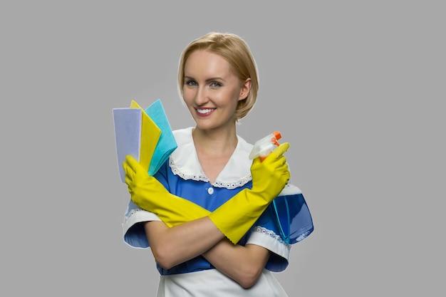 Mooi kamermeisje met schoonmaakspray en vodden. jonge mooie vrouw meid schoonmaak leveringen te houden en camera te kijken.