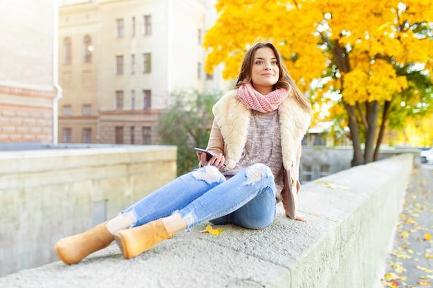 Mooi kaukasisch donkerbruin meisje die warme de herfstdag met achtergrond van bomen met geel gebladerte en een stad zitten