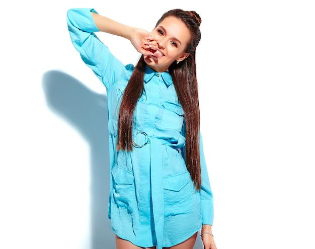 Mooi kaukasisch het glimlachen donkerbruin vrouwenmodel in heldere blauwe de zomer modieuze die kleding op witte achtergrond wordt geïsoleerd. haar vinger bijten