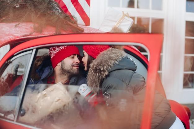Mooi kaukasisch meisje in warme winterkleren draagt dozen met kerstcadeaus in een rode auto naar haar man