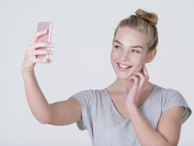 Mooi kaukasisch meisje maakt selfies. gelukkig prachtige vrouw met mobiele telefoon in handen