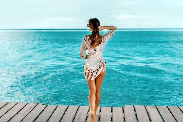 Mooi kaukasisch meisje met bruin haar in de zomerkleding die zich op het dok bevindt en water bekijkt.