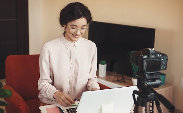 Mooi kaukasisch meisje met een online conferentie achter de laptop voor de camera