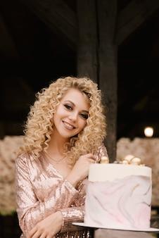 Mooi kaukasisch meisje met krullend haar glimlacht ter ere van haar verjaardag met een feestelijke stijlvolle taart