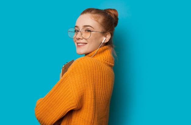 Mooi kaukasisch meisje met rood haar en sproeten houdt haar laptop vast en gebruikt een koptelefoon op een blauwe muur met vrije ruimte