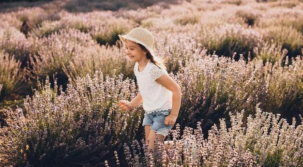 Mooi kaukasisch meisje met wit overhemd en hoed die in een lavendelgebied loopt en op een zonnige dag glimlacht