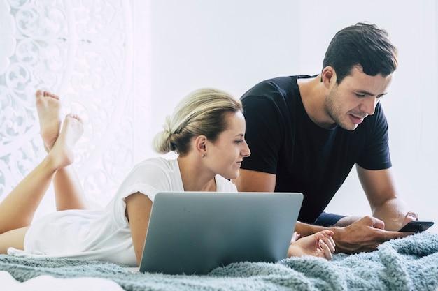 Mooi kaukasisch paar dat thuis in de slaapkamer op bed ligt en werkt en technologie-notebooklaptop en mobiele telefoon gebruikt