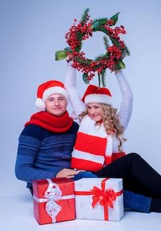 Mooi kerstpaar in santa claus-hoeden met cadeautjes op blauwe achtergrond