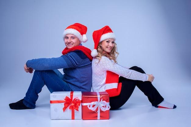Mooi kerstpaar zittend met cadeautjes