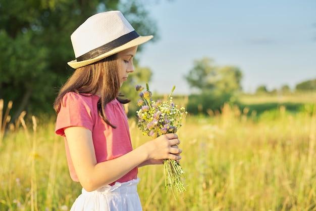 Mooi kind meisje in hoed, jurk in veld scheurend boeket van wilde bloemen, gouden uur, met kopieerruimte. schoonheid, natuur, vrije tijd, gelukkige jeugd, zomervakantie concept
