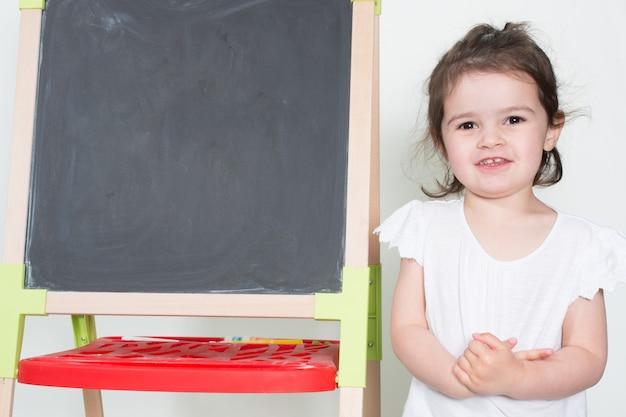 Mooi kind meisje spelen terug naar school met speelgoed schoolbord