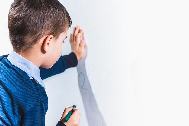 Mooi kind tekent op de muur met kleurpotloden