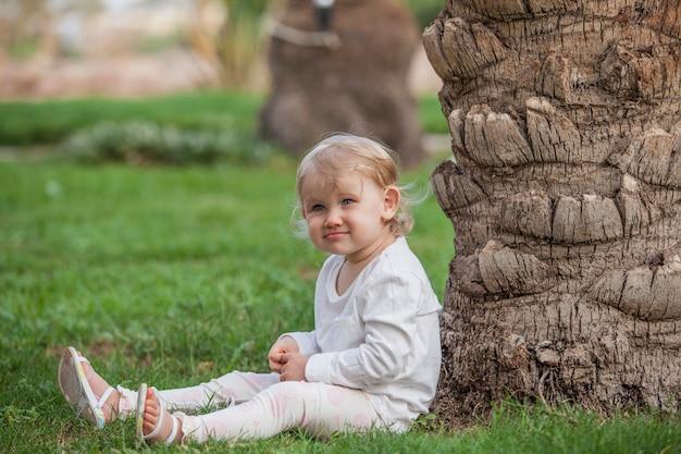 Mooi kind zit aan de stam van de palmboom in tropicalism park. gazon, zomer, boom, vakantie, reis