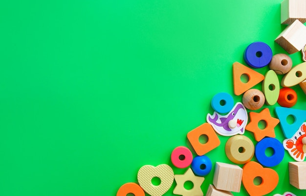 Mooi kinderspeelgoed is neergelegd op een bovenaanzicht van een groene achtergrond. ruimte voor tekst