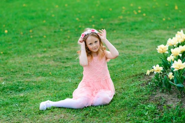 Mooi kindmeisje die en in bloemen van de tuin glimlachen glimlachen, bloeiende bomen, kers, appelen.