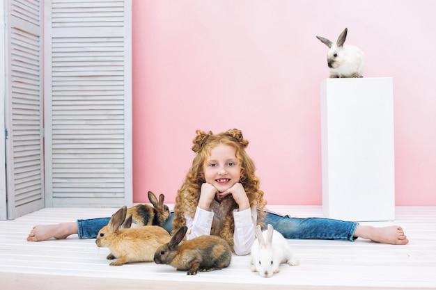 Mooi kindmeisje met krullend haar en met pluizige dierenkonijnen op roze achtergrond