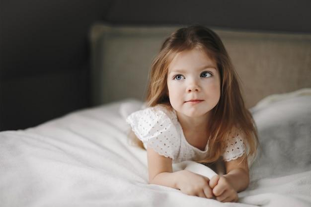 Mooi kindmodel ligt op de witte deken op het bed en kijkt naar de zijkant