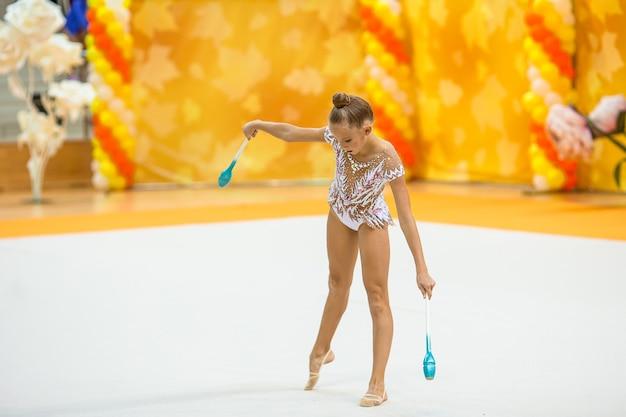 Mooi klein actief turnstermeisje met haar optreden op het tapijt