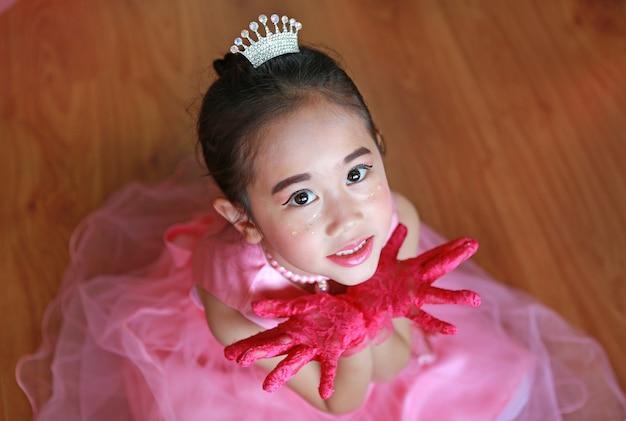 Mooi klein aziatisch ballerinameisje in een roze tutuuitdrukking overhandigt open.
